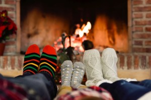 Feet in Christmas socks near fireplace. Family relaxing at home.